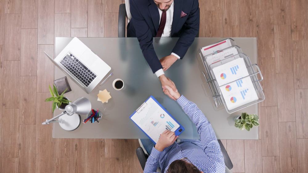 top view businessmen shaking hands during business negotiation startup office האם גישור עסקי מתנהל בצורה אחרת מאשר סוגי גישור אחרים?